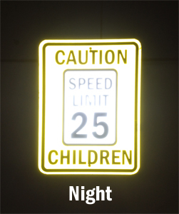 Reflective speed limit sign visible in the night