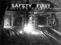 Safety First reflective sign over train tracks