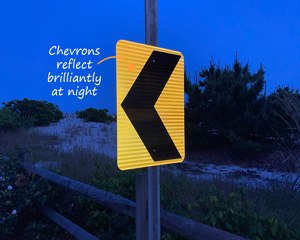 Road chevron sign reflects at night